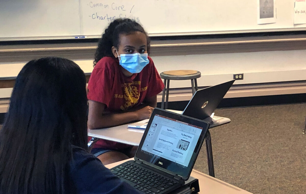 Two students in a classroom talk to each other while wearing masks