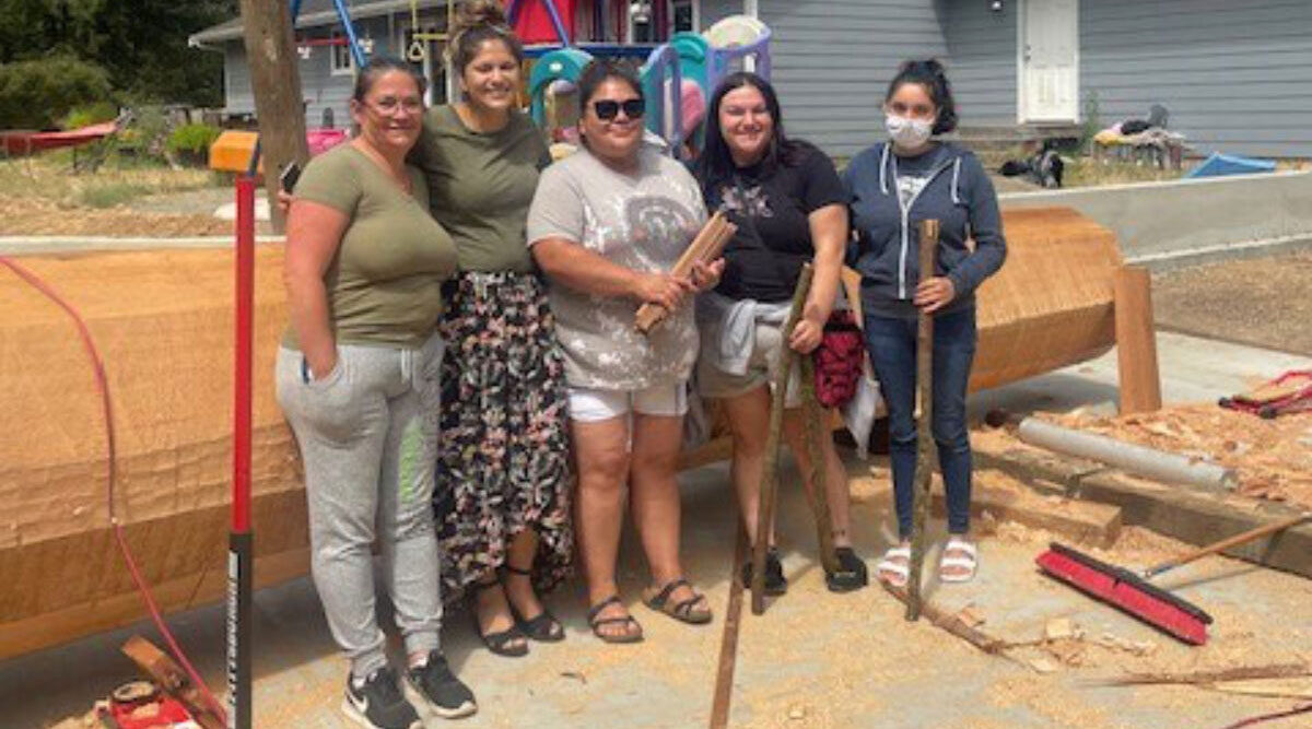 Artist Andrea Wilbur Sigo and students stand together in front of a large log