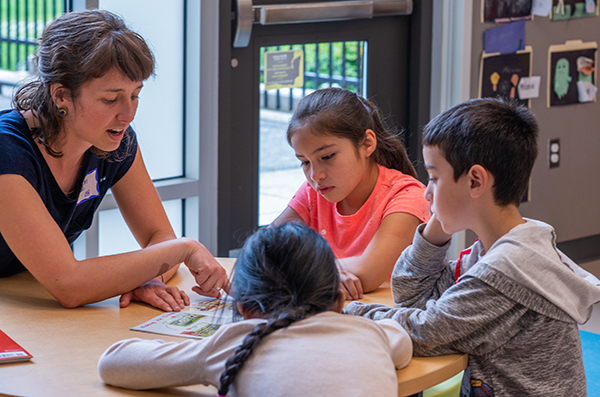 A teacher talks with three young students at a table.