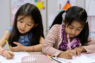 Two young students write on papers together at a desk in a classroom.