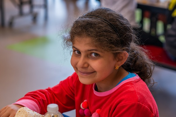 A girl smiles at the camera while eating lunch at school