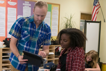 A student and teacher talk in a classroom while holding a tablet