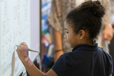 A young student works at a white board in a classroom