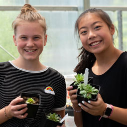 Two high school students smile for a photo while holding small plants in a greenhouse.