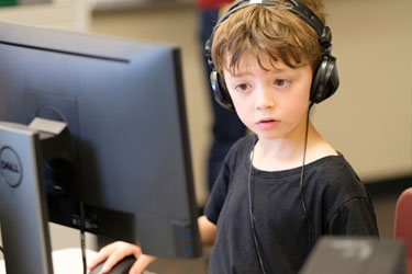 A young student sits at a computer with headphones