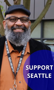 """A man smiles for a photo with text """"Support Seattle"""""""