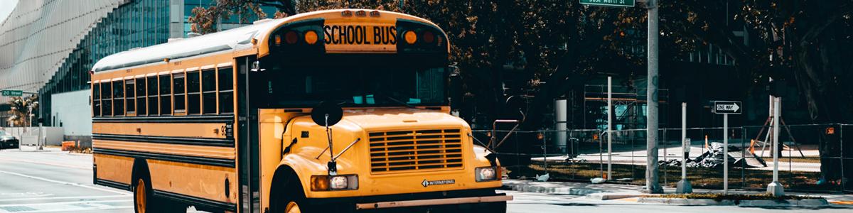 A school bus drives on a city street