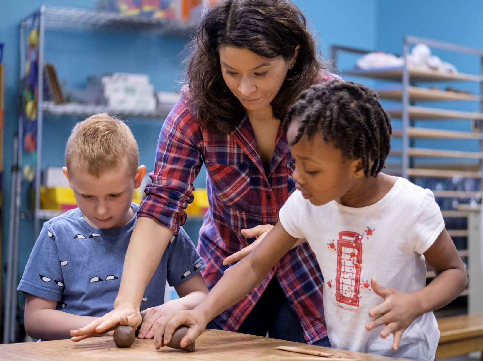 teacher working with two elementary students on a clay project