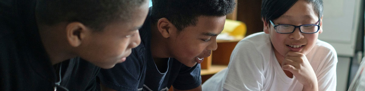 Three middle school age students talk together in a classroom.