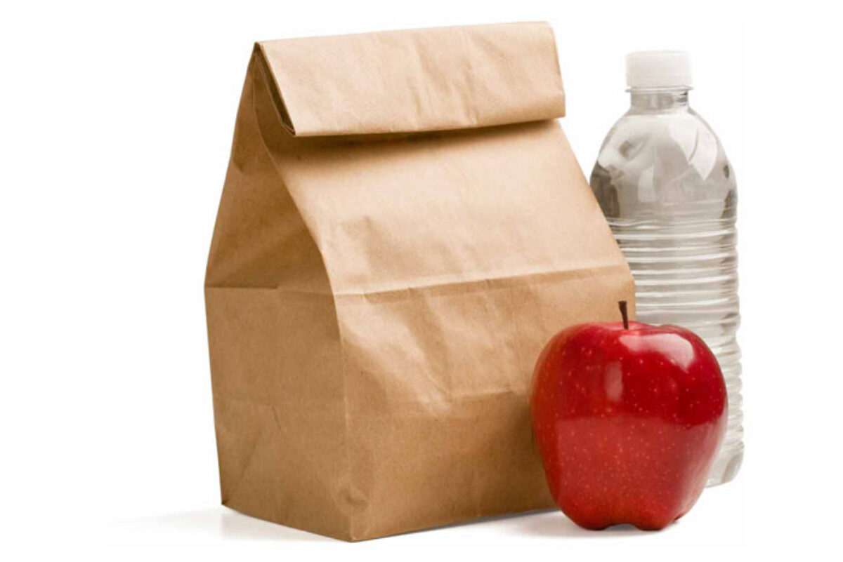 A sack lunch with an apple and bottle of water.