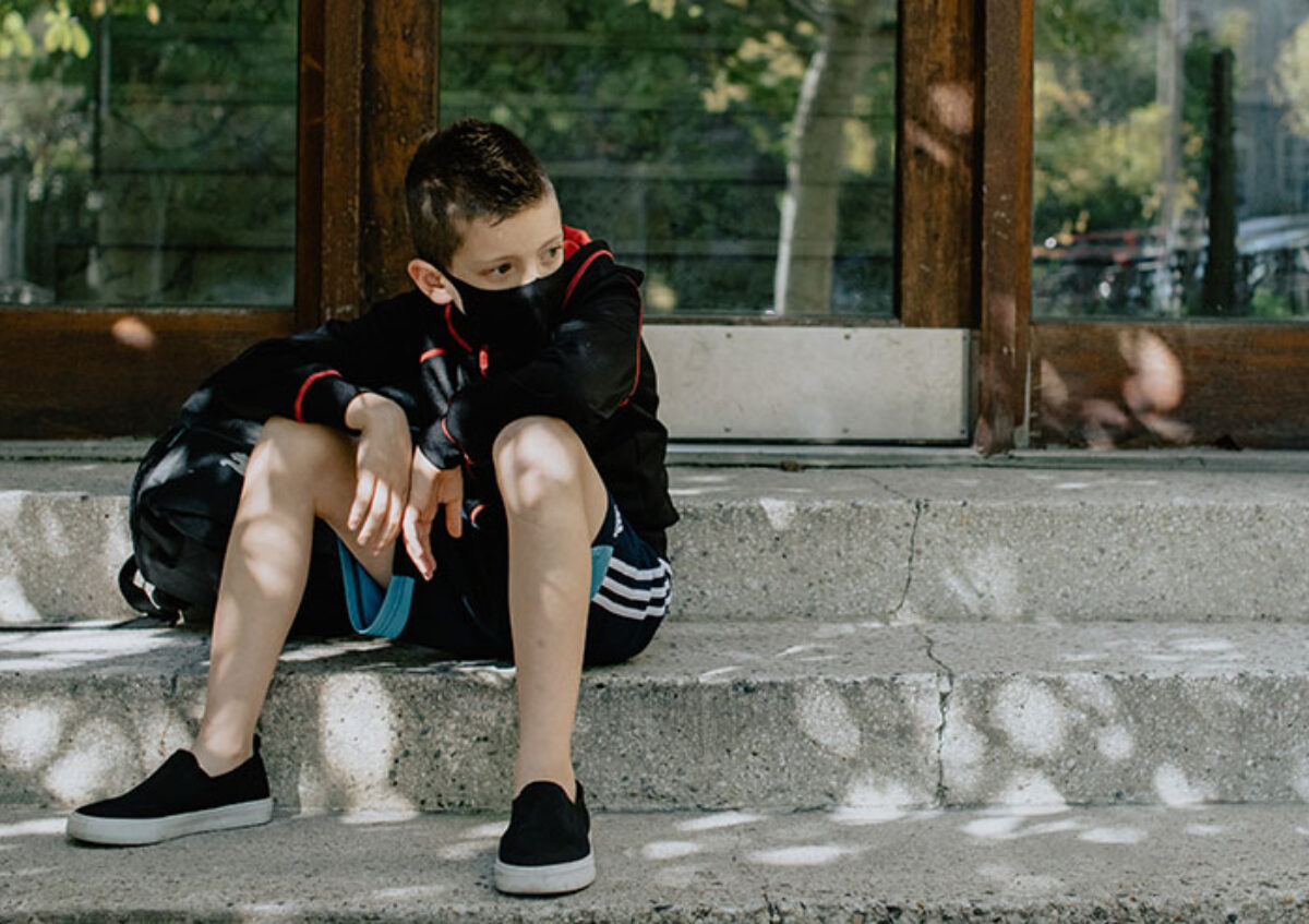 A student sits outside a school building in a mask