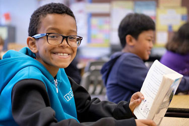 A student holds a book and smiles for a photo