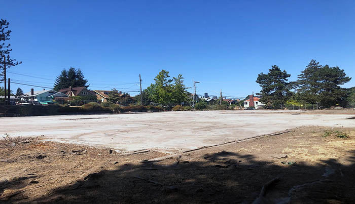 a concrete slab with dirt surrounding it and houses in the distance