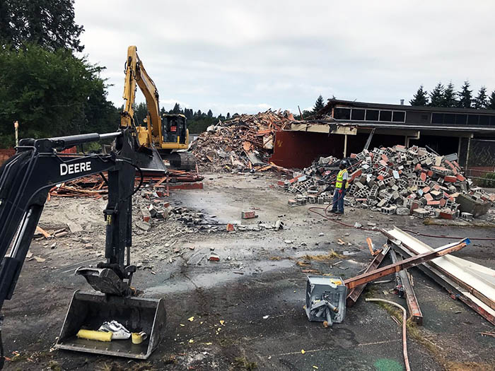 a demolition site with heavy equipment and piles of debris in front of a partially demolished building