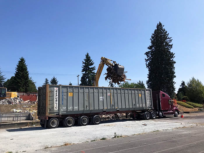 a container truck with machinery loading debris into it