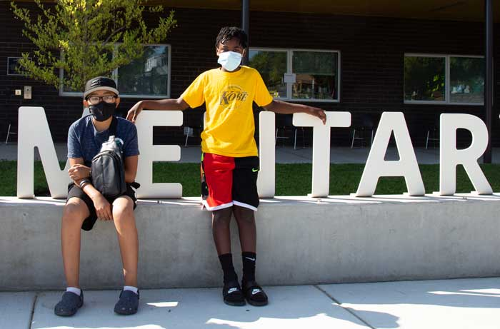 Two students stand together outside wearing masks in front of a school