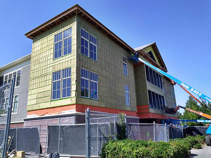 siding being installed on a 3-story building by a person in a lift