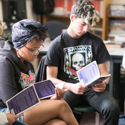 Students sit together in a classroom reading the same book.