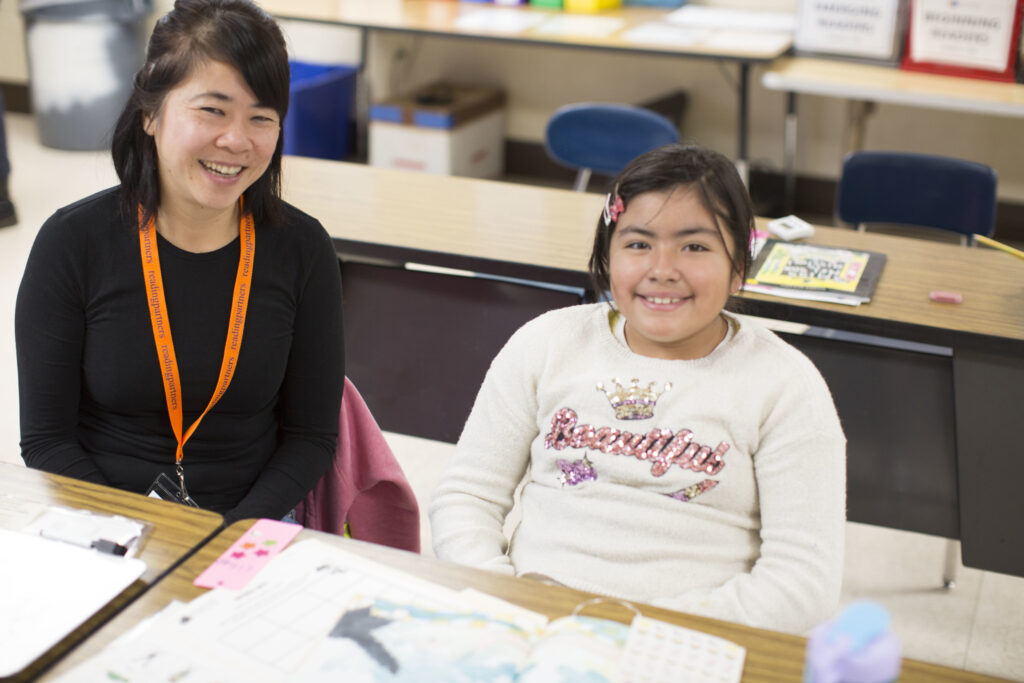 Volunteer tutor and a student sitting at a desk in a classroom side-by-side smiling.