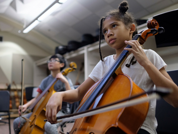 Two middle school students play string intstruments in a classroom.